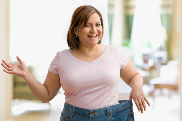 Woman holding waistbands of jeans that are too big
